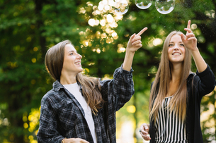 Two young female friends bursting floating bubbles in parkの写真素材 [FYI03596970]