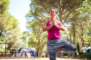 Mature woman practicing yoga tree pose on camping siteの写真素材 [FYI03596973]