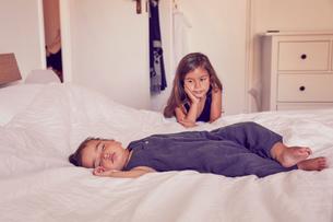Female toddler, sleeping on bed, older sister watching her sleepの写真素材 [FYI03597025]