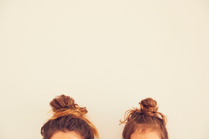 Portrait of mother and daughter, hair in bun, top sectionの写真素材 [FYI03597039]
