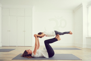 Mother and daughter in yoga studio, daughter balancing on mothers legsの写真素材 [FYI03597051]