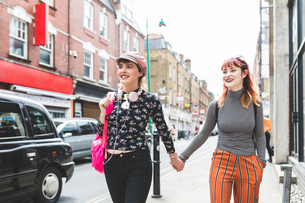 Two retro styled young women strolling on city street holding handsの写真素材 [FYI03597118]