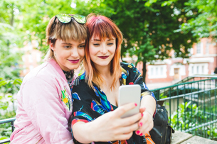 Two retro styled young women taking smartphone selfie in parkの写真素材 [FYI03597125]