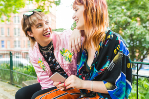 Two retro styled young women laughing in parkの写真素材 [FYI03597126]