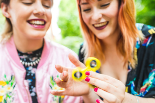 Two retro styled young women playing with fidget spinner in parkの写真素材 [FYI03597128]