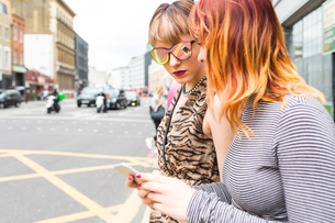 Two retro styled young women strolling along city street looking at smartphoneの写真素材 [FYI03597131]