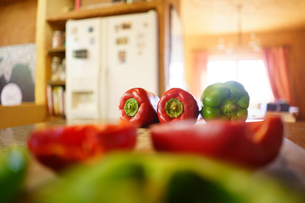 Whole and half red and green peppers on kitchen counterの写真素材 [FYI03597144]