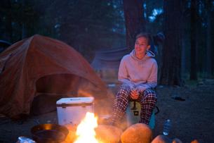 Teenage boy sitting beside camp fireの写真素材 [FYI03597153]