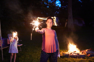 Two girls standing near camp fire, using sparklersの写真素材 [FYI03597355]
