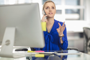 Young female office worker making smartphone call at deskの写真素材 [FYI03597395]