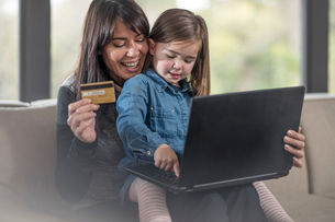 Girl and mother on sofa using laptop and credit card for online shoppingの写真素材 [FYI03597508]