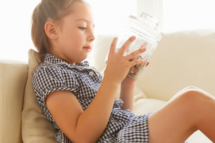 Young girl, relaxing on sofa, holding jar of money, pensive expressionの写真素材 [FYI03597656]