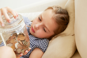 Young girl, relaxing on sofa, holding jar of money, pensive expressionの写真素材 [FYI03597658]