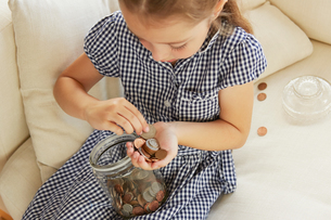 Young girl, sitting on sofa, counting money from jar, elevated viewの写真素材 [FYI03597659]