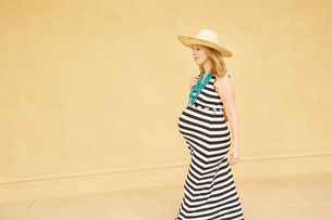 Pregnant woman walking by yellow wallの写真素材 [FYI03597667]