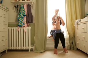 Pregnant woman and daughter in bedroomの写真素材 [FYI03597682]
