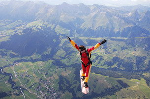 High angle view of skydiver surfing on sky board over mountainsの写真素材 [FYI03597696]