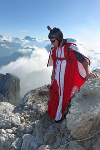 Male wingsuit BASE jumper preparing to fly from cliff edgeの写真素材 [FYI03597699]