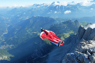 Male wingsuit BASE jumper taking off from cliff edgeの写真素材 [FYI03597700]