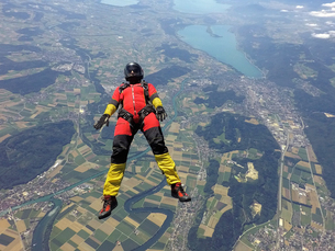 Female skydiver free falling on back above landscapeの写真素材 [FYI03597702]