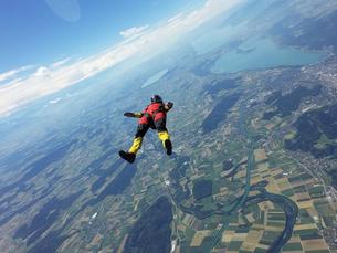 Female skydiver free falling on back above landscapeの写真素材 [FYI03597704]