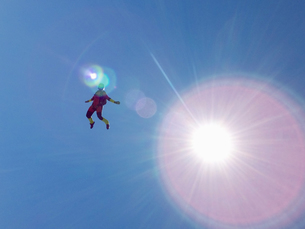 Female skydiver free falling upright against sunlit blue skyの写真素材 [FYI03597706]