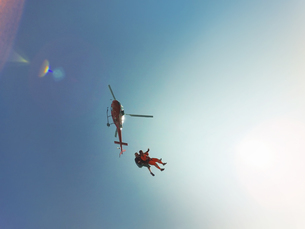 Low angle view of tandem skydiving jump from a helicopter  against sunlit blue skyの写真素材 [FYI03597707]
