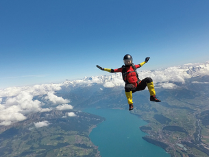 Female skydiver sitting up in free fall above clouds and lakeの写真素材 [FYI03597709]