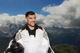 Portrait of base jumper wearing wingsuit looking away smiling, Dolomite mountains, Canazei, Trentinoの写真素材 [FYI03597714]