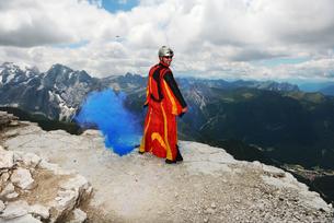 Base jumper on Dolomite mountains wearing wingsuit emitting blue smoke, Canazei, Trentino Alto Adigeの写真素材 [FYI03597720]