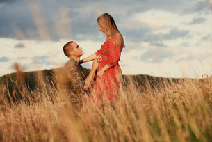 Mid adult man kneeling with hand on pregnant wife's stomach in fieldの写真素材 [FYI03597827]