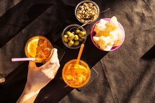 Overhead view of sidewalk cafe table with woman's hand holding aperitif, Riccione, Emilia-Romagna, Iの写真素材 [FYI03597872]