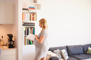Pregnant young woman in living room with cook bookの写真素材 [FYI03597919]