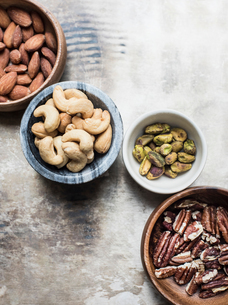 Variety of mixed nuts in bowls, close-upの写真素材 [FYI03598040]