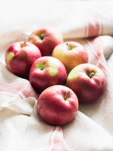 Six red apples on linen kitchen cloth, close-upの写真素材 [FYI03598041]