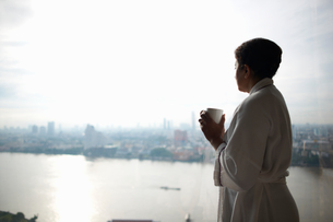 Woman wearing dressing gown holding cup looking away at view of city, Bangkok, Krung Thep, Thailand,の写真素材 [FYI03598105]