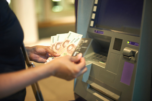 Cropped view of woman withdrawing money from cash machineの写真素材 [FYI03598110]