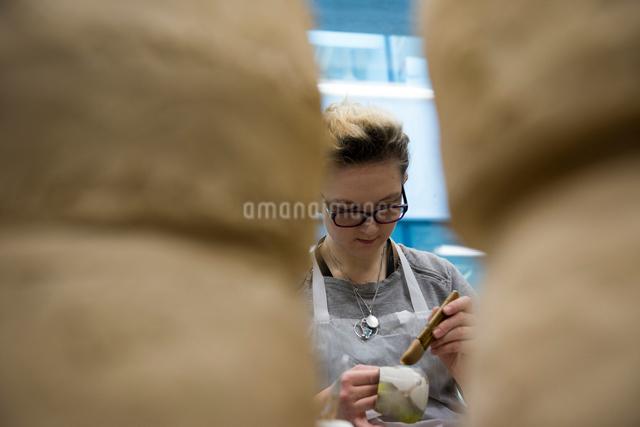 Woman in art studio glazing potteryの写真素材 [FYI03598441]