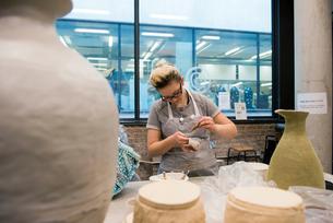 Woman in art studio glazing potteryの写真素材 [FYI03598442]