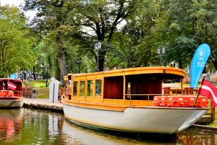 ラトビア・首都リガのダウガヴァ川を巡る観光船から見た緑の木々の映り込みと観光船のある景観の写真素材 [FYI03598501]
