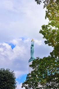 ラトビア・首都リガのダウガヴァ川を巡る観光船から見た旧市街にある自由記念碑(ラトビア独立戦争(1918-1920)で殺された兵士に捧げられている。 ラトビアの自由、独立、主権のシンボル)の写真素材 [FYI03598539]