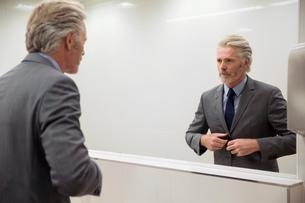 Mirror image of man looking into mirrorの写真素材 [FYI03598560]