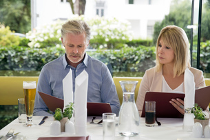 Couple al fresco dining at restaurant, selecting from menuの写真素材 [FYI03598571]