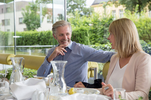 Smiling couple al fresco dining at restaurantの写真素材 [FYI03598574]