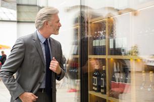 Man window shopping in wine shop windowの写真素材 [FYI03598580]