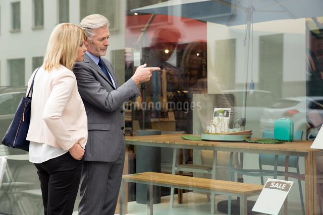 Couple window shopping in homewares shop windowの写真素材 [FYI03598582]