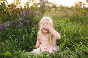 Girl sitting in tall grass, hand covering eyesの写真素材 [FYI03598604]