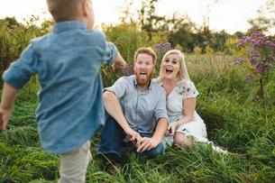 Boy surprising parents sitting in tall grassの写真素材 [FYI03598616]