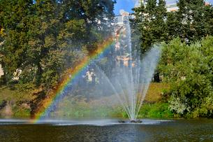 ラトビア・首都リガのダウガヴァ川を巡る観光船から見た緑の木々と噴水の虹のある景観の写真素材 [FYI03598619]