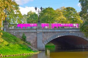 ラトビア・首都リガのダウガヴァ川を巡る観光船から見た緑の木々とトラムの走る景観の写真素材 [FYI03598658]